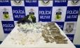 Pistola, drogas e rádio transmissor. Material foi apreendido por policiais durante ação na Cidade de Deus Foto: Divulgação/PM