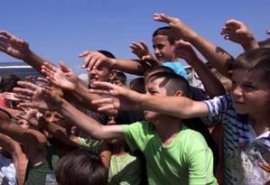 Crianças refugiadas da antiga Iugoslávia erguem as mãos para receber ajuda humanitária em 1999 ; grupo é um dos mais afetados pela Síndrome da Resignação, registrada na Suécia desde 1998 Foto: Laszlo Balogh / Reuters