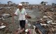 Homem caminha em meio a destroços de tsunami na Indonésia, em 2005 Foto: Yusuf Ahmad / Reuters