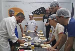Mão na massa. Professor do Colégio Eduardo Guimarães com alunos na aula de Gastronomia Foto: Divulgação