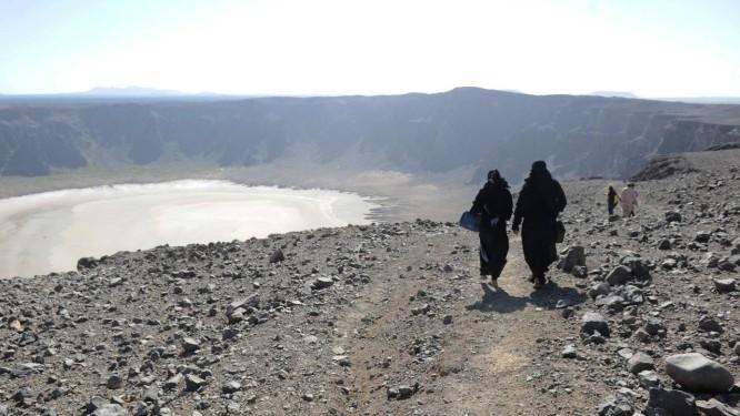 Mulheres sauditas caminham perto da cratera vulcânica do deserto de Al-Wahbah, na Arábia Saudita: país quer promover o lugar, pouco frequentado, como destino turístico Foto: AMER HILABI / AFP