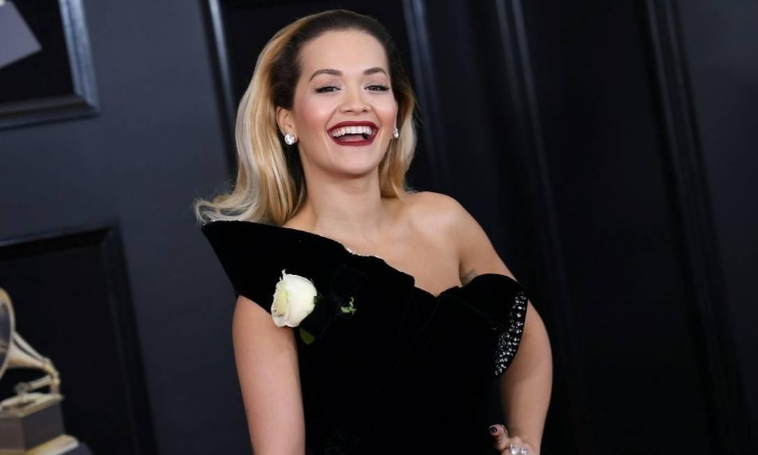 Rita Ora vestiu preto e colocou a flor branca do #timesup ANGELA WEISS / AFP