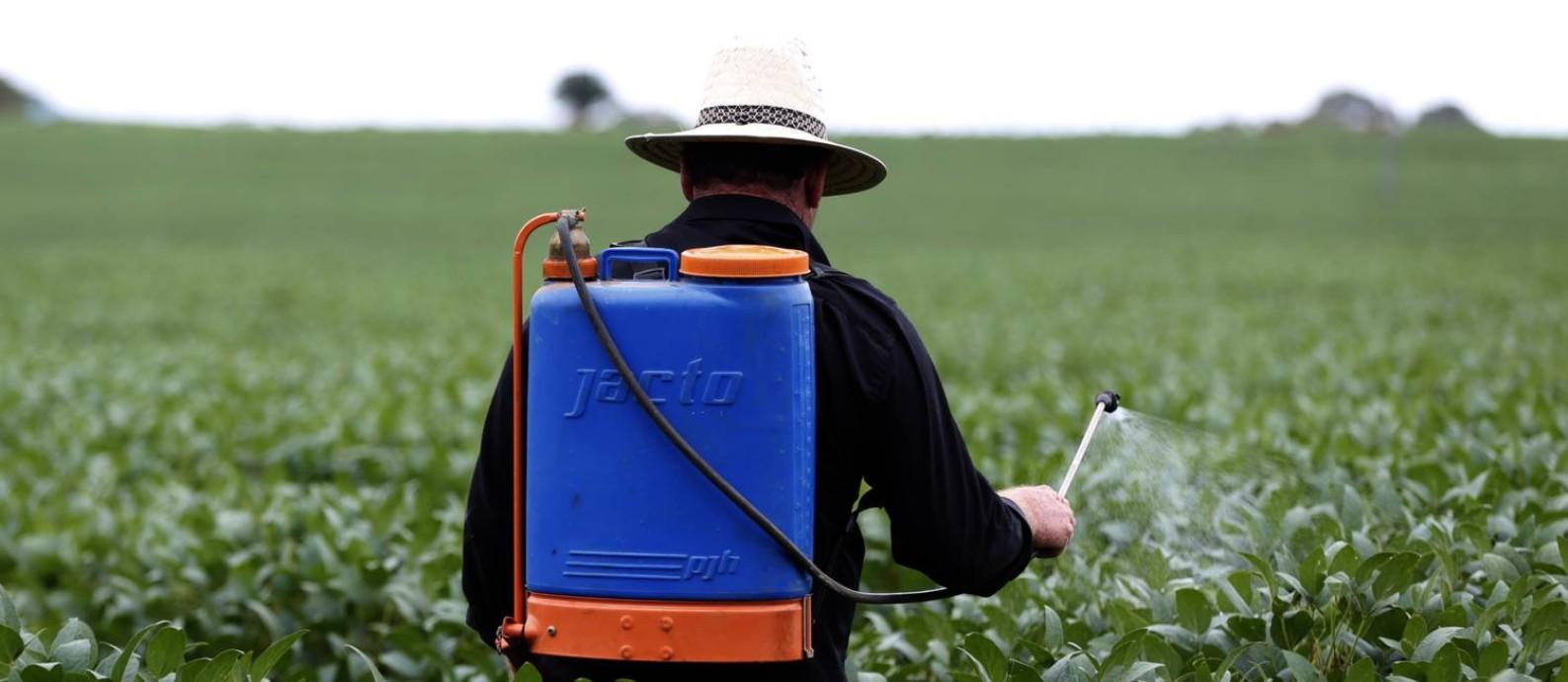 O agricultor Adilson Pagani aplica pesticida na plantação de soja sem proteção adequada Foto: Michel Filho / Agência O Globo