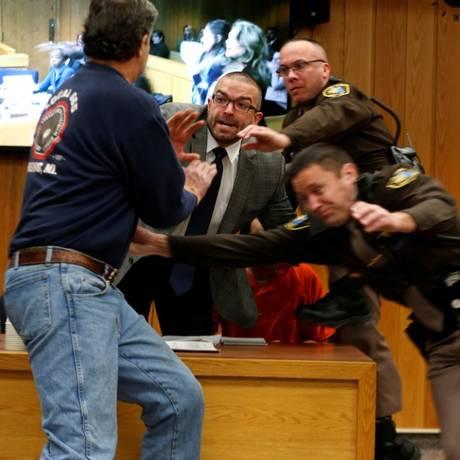 Randall Margraves, em primeiro plano, tenta agredir o ex-médico Larry Nassar, ao fundo, com roupa laranja Foto: REBECCA COOK / REUTERS