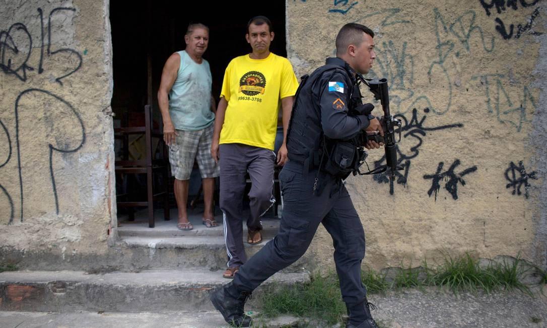 Moradores observam movimentação de policial armado em mais um dia de operação na Cidade de Deus Foto: MAURO PIMENTEL / AFP