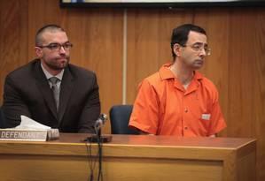 Larry Nassar ao lado do advogado Matt Newburg enquanto ouve a sentença pronunciada pela juíza Janice Cunningham por crimes de abuso sexual em Charlotte, Michigan. Foto: SCOTT OLSON / AFP