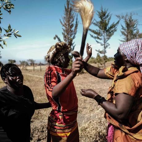 Mulher reproduz parte da cerimônia de circuncisão, em Uganda Foto: YASUYOSHI CHIBA / AFP