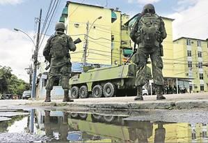 De volta às ruas. Diante de um veículo blindado, militares montam guarda em frente a um bloco de edifícios da Cidade de Deus: operação em quatro comunidades do Rio mobilizou cerca de 3 mil homens das Forças Armadas Foto: Antonio Scorza