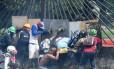 Manifestantes sob a mira da arma de um agente da Guarda Nacional nas manifestações na Venezuela em maio de 2017