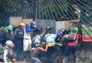 Manifestantes sob a mira da arma de um agente da Guarda Nacional nas manifestações na Venezuela em maio de 2017 Foto: JUAN BARRETO / AFP
