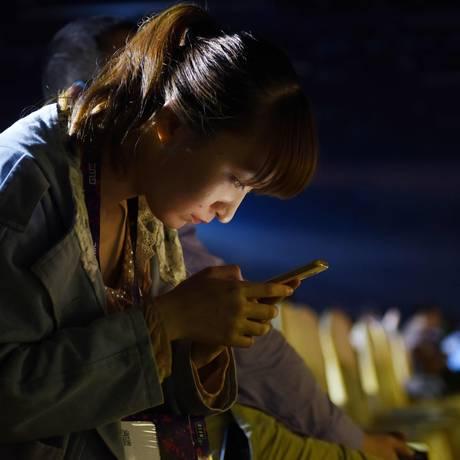 Chinesa usa celular Foto: Greg Baker/AFP/27-4-2017