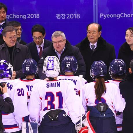 O presidente da Coreia do Sul, Moon Jae-in; o presidente do Comitê Olímpico Internacional, Thomas Bach; e a líder da comitiva da Coreia do Norte, Kim Yo-jong, conversam com as atletas do time coreano unificado de hóquei no gelo feminino Foto: JUNG YEON-JE / AFP