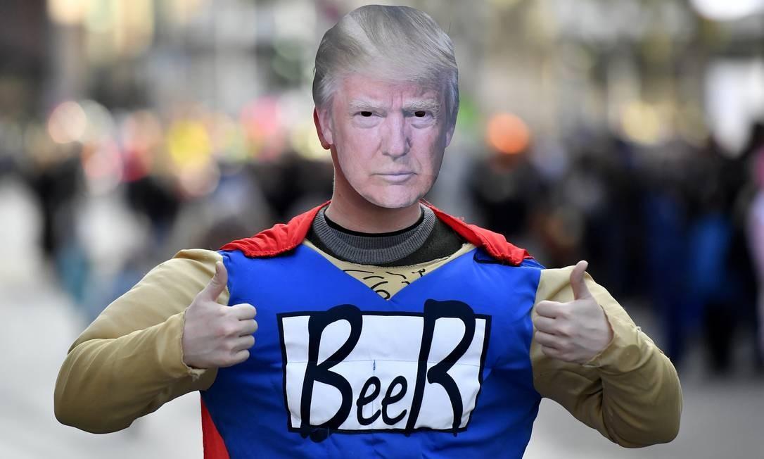 Com uma máscara de Trump, o folião deixa claro do que realmente gosta no carnaval de Dusseldorf, na Alemanha: CervejA Foto: Martin Meissner / AP