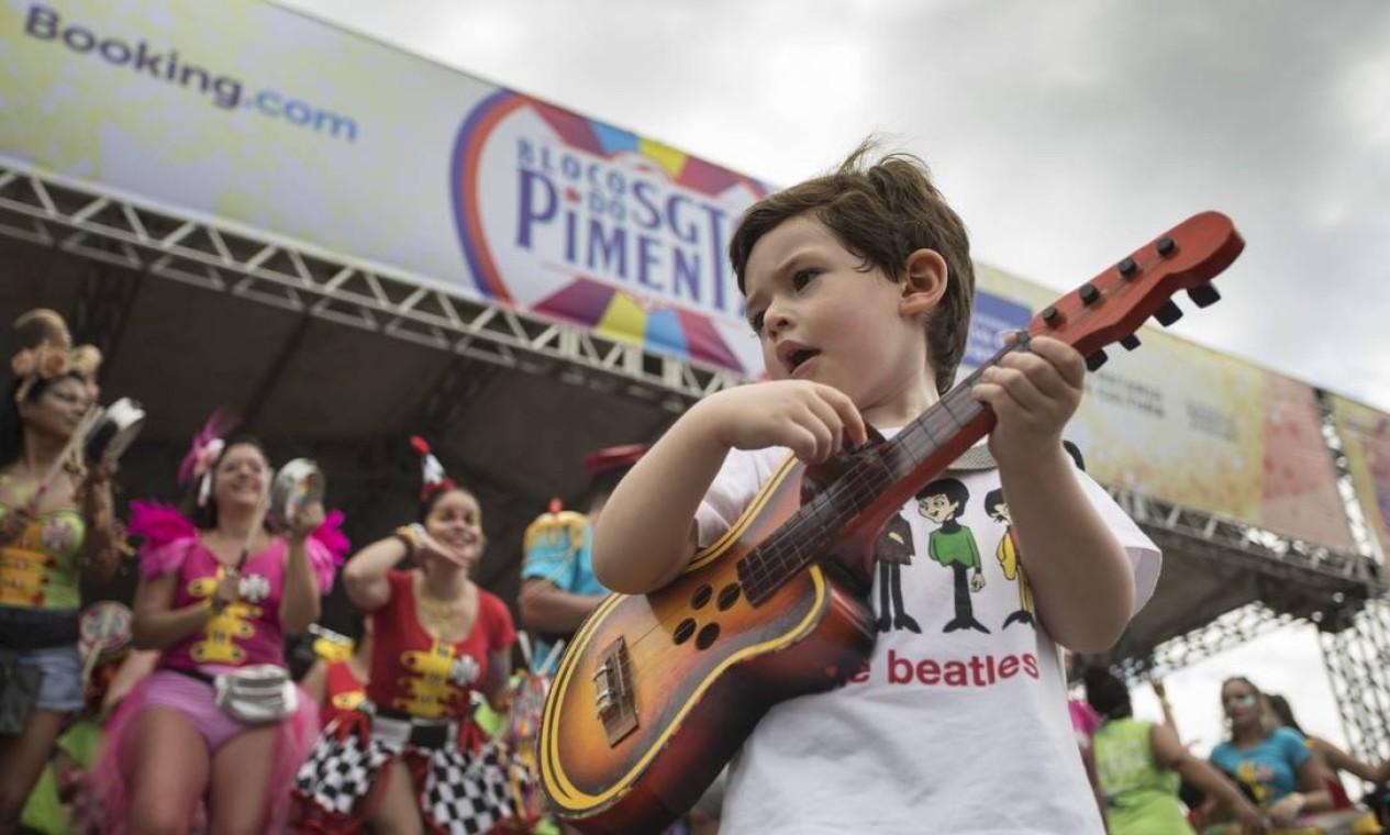 O pequeno Raul Garcia roubou a atenção com sua guitarra de brinquedo, que acompanhava os sucessos do bloco Foto: Ana Branco / Agência O Globo