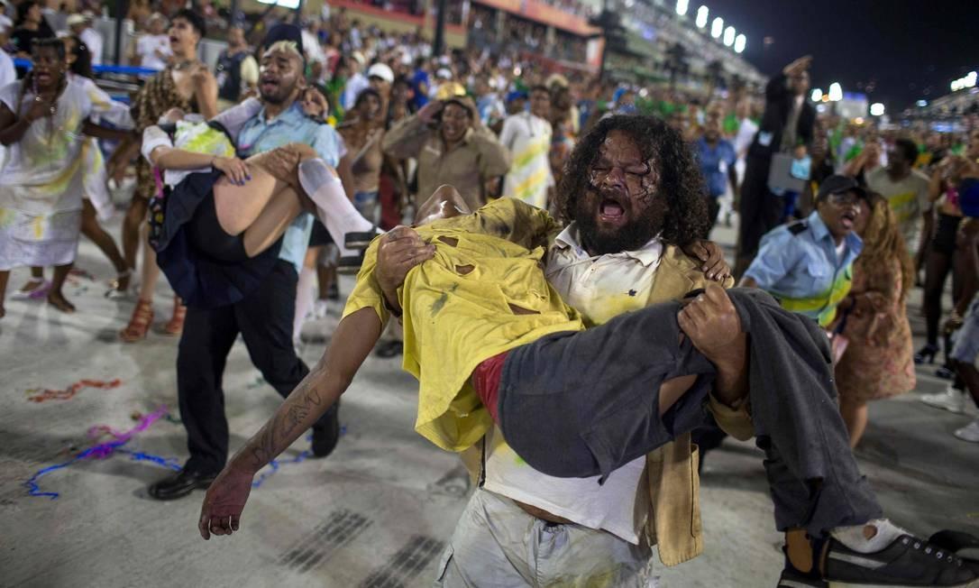 Em um enredo que tratava das mazelas do Brasil, componentes carregavam vítimas de arma de fogo MAURO PIMENTEL / AFP