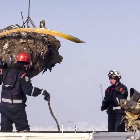 Destroços de um dos motores do avião são transportados por funcionários dos serviços de emergência Foto: AP