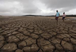 Cenário desolador. Uma família anda pela barragem de Theewaterskloof, a principal fonte de água da Cidade do Cabo: praticamente seca Foto: MIKE HUTCHINGS / MIKE HUTCHINGS/REUTERS