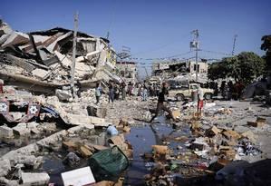 Devastação. Em Porto Príncipe, haitianos checam os efeitos do terremoto que arrasou o país em 2010; ONG britânica é acusada de encobertar denúncias de abusos sexuais Foto: OLIVIER LABAN-MATTEI / AFP/15-1-2010