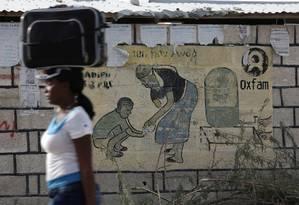 Haitiana caminha por parede com mensagem da Oxfam em Porto Príncipe. Escândalo no Haiti pode afetar trabalho da ONG em todo o mundo Foto: ANDRES MARTINEZ CASARES / REUTERS