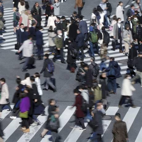 Pedestres cruzam a rua em Shibuya, distrito de Tóquio. Foto: Eugene Hoshiko/AP