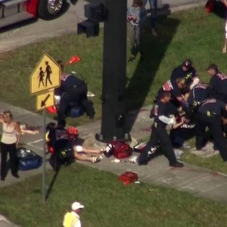 Pessoas são atendidas perto da escola de ensino médio Marjory Stoneman Douglas, na Flórida Foto: Reprodução da TV