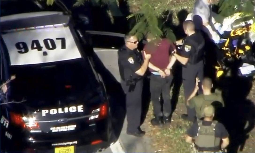 Nicolas Jesus Cruz é levado algemado por policiais. Ele é apontado como o atirador que matou mais de 15 pessoas na escola de ensino médio Marjory Stoneman Douglas, em Parkland, Flórida Foto: . / REUTERS