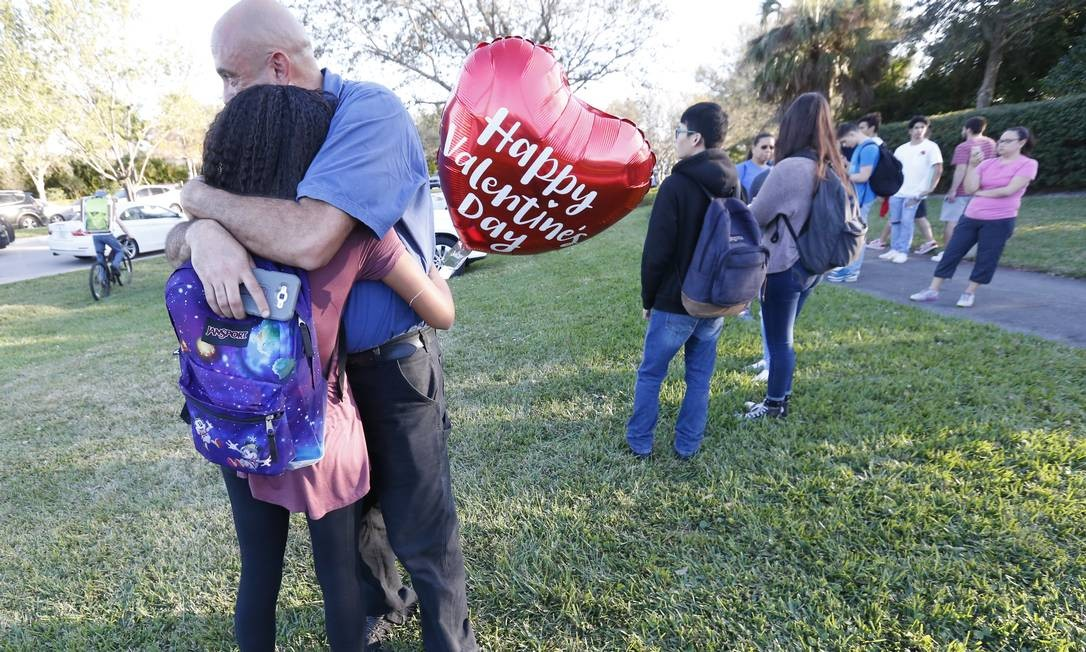 Parentes de alunos se abraçam diante da escola Marjory Stoneman Douglas após o ataque Foto: Wilfredo Lee / AP