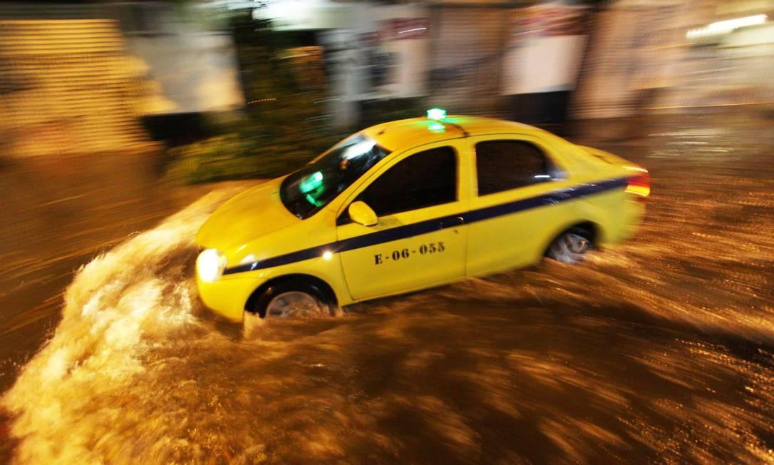 Táxi passa pela Rua Dezenove de Fevereiro, em Botafogo, totalmente inundada Foto: Paulo Nicolella / Agência O Globo