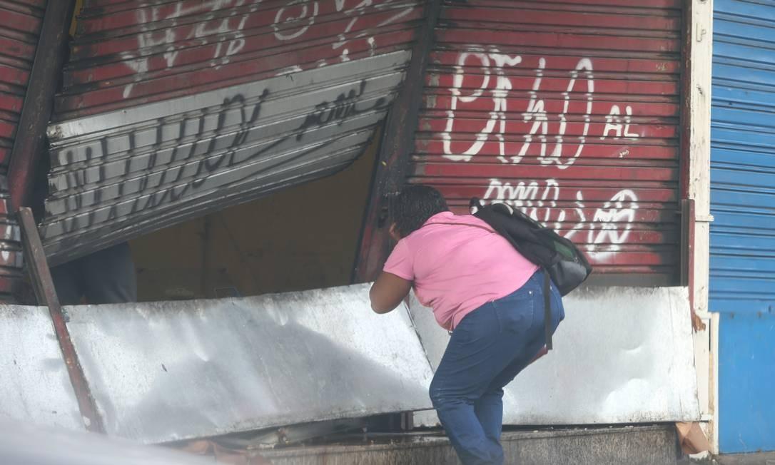 Uma mulher olha destruição causada pela força da água em uma loja em Quintino, na Zona Norte Foto: Fabiano Rocha / Agência O Globo