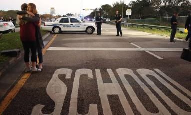 Policiais e parentes de vítimas em frente à escola Marjory Stoneman Douglas, vítima de ataque a tiros, em Parkland, na Flórida Foto: MARK WILSON / AFP