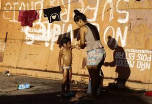Imigrante dá banho em menina no Ginásio Tancredo Neves Foto: Jorge William / Agência O Globo