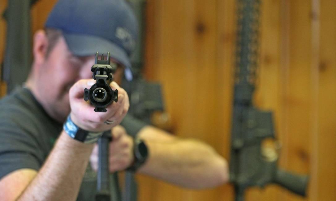 Homem mostra AR-15, fuzil usado no massacre que matou 17 pessoas em escola da Flórida em fevereiro de 2018 Foto: GEORGE FREY / AFP