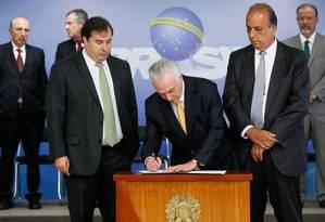 O presidente Temer assina o decreto de intervenção na segurança do Rio, ao lado de Maia e Pezão Foto: Agência Brasil
