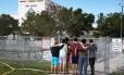 Pessoas observam os portões fechados do colégio Marjory Stoneman Douglas, onde 17 pessoas foram mortas pelo atirador Nikolas Cruz Foto: JOE RAEDLE / AFP