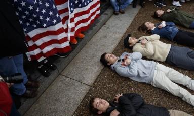 Manifestantes fazem protesto deitado diante da Casa Branca Foto: Evan Vucci / AP
