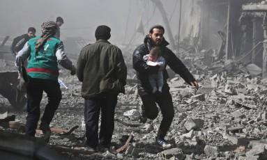 Sírio carrega criança ferida em bombardeio em Hamouria, em Ghouta Oriental Foto: ABDULMONAM EASSA / AFP