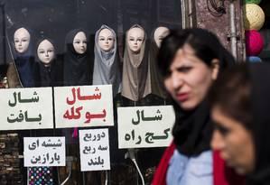 Iranianas passam por loja em Teerã exibindo véus Foto: BEHROUZ MEHRI / AFP/24-2-2016