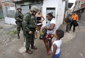 Uma militar revista mochila de menino durante operação na Favela Kelson's Foto: Domingos Peixoto / Agência O Globo