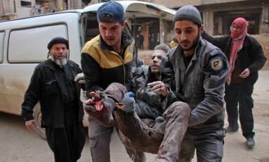Voluntários da Defesa Civil conhecidos como Capacetes Brancos carregam homem ferido após bombardeio aéreo em Douma, na região de Ghouta Foto: HAMZA AL-AJWEH / AFP