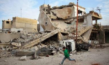 Menino sírio corre na rua destruída por bombardeios no Leste de Ghouta Foto: HAMZA AL-AJWEH / AFP