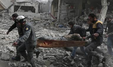 Membros da Defesa Civil síria retiram um civil ferido durante o bombardeio a Ghouta Oriental Foto: ABDULMONAM EASSA / AFP