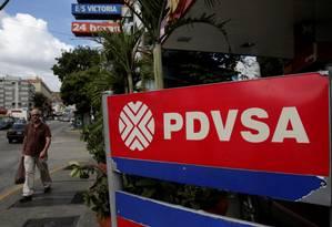 Homem passa em frente a placa com nome da companhia petroleira estatal venezuelana (PDVSA) em posto de gasolina de Caracas Foto: Marco Bello / Reuters