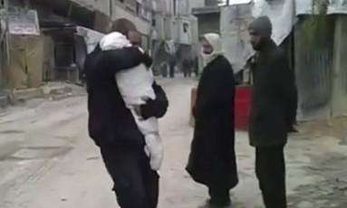Um vídeo divulgado pelo grupo ativista Ghouta Media Center mostra o momento em que um pai se despede de seu filho, morto em bombardeios na Síria Foto: Ghouta Media Center / AP