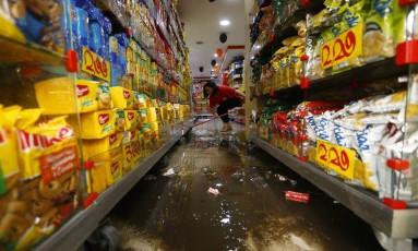 Mulher limpa a sujeira deixada pela chuva em loja de Copacabana Foto: Pablo Jacob / Agência O Globo
