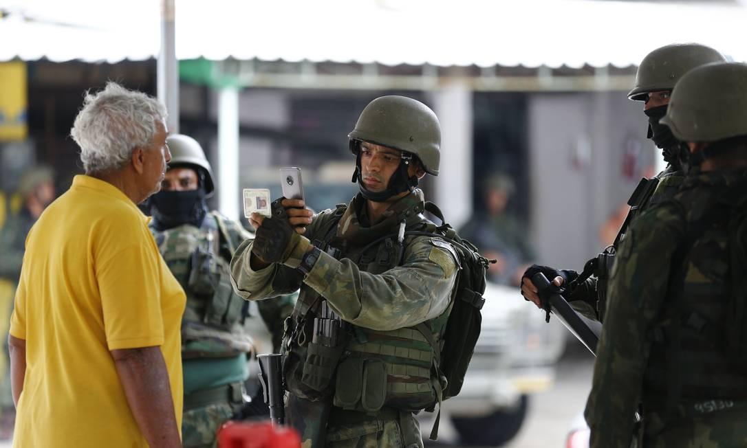 Homem é fotografado junto com o documento de identificação Foto: Pablo Jacob / Agência O Globo