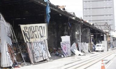 Estrutura comprometida. Máquinas removem lixo para evaziar barracão Foto: Fábio Guimarães / Agência O Globo