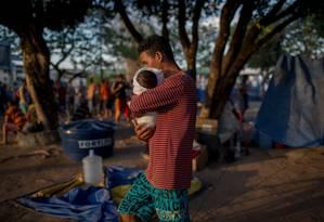 Imigrante venezuelano carrega bebê em campo de acolhimento improvisado em Boa Vista, Roraima Foto: Mauro Pimentel / AFP
