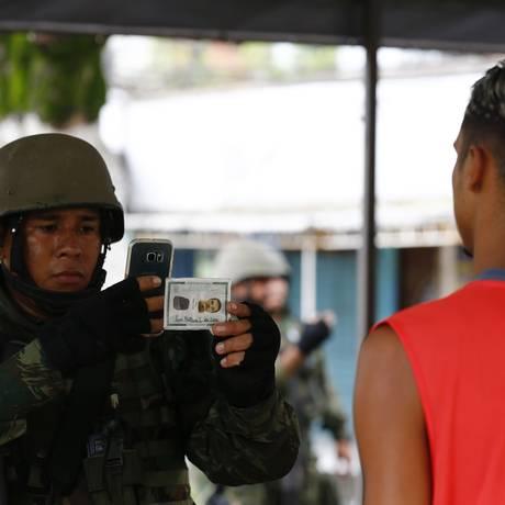 Militares 'ficham' moradores durante operação conjunta na Vila Kennedy Foto: Pablo Jacob/Agência O Globo/23-02-2018