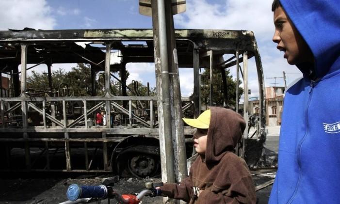 Jovens passam por ônibus incendiado em São Paulo em 15-05-2006 Foto: Victor R. Caivano / AP