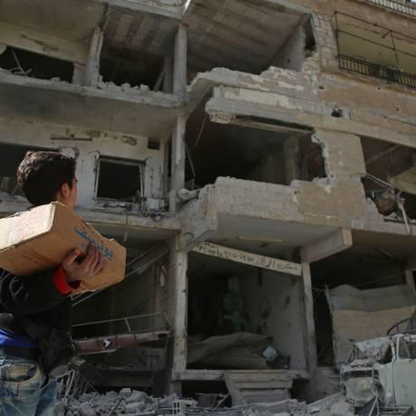 Menino sírio passa por prédio parcialmente destruído em Kafar Batna, Ghouta Oriental: impedidos de sair, apesar do cessar-fogo Foto: AMER ALMOHIBANY / AFP
